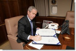 President George W. Bush signs into law H.R. 2764, the Consolidated Appropriations Act 2008, also known at the omnibus, making appropriations for the Department of State, foreign operations, and related programs for the fiscal year ending September 30, 2008, and for other purposes, after boarding Air Force One Wednesday, Dec. 26, 2007. White House photo by Chris Greenberg